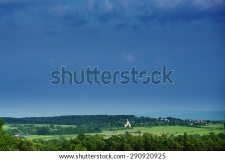 far in the distance houses trees sky fields landscape meadows - stock photo