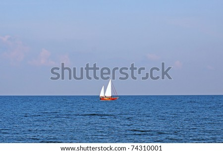 Far red boat with white sail far on the sea