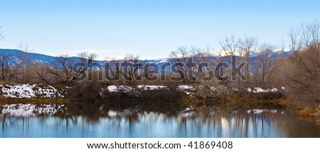 Far shore of a small lake with reflections and view of distant Rocky Mountains - stock photo
