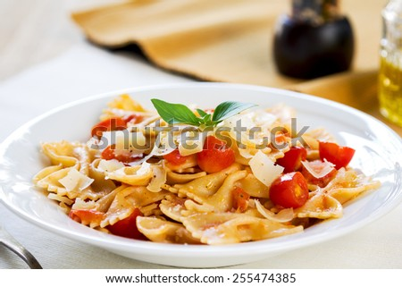 Farfalle in tomato sauce with grated parmesan - stock photo