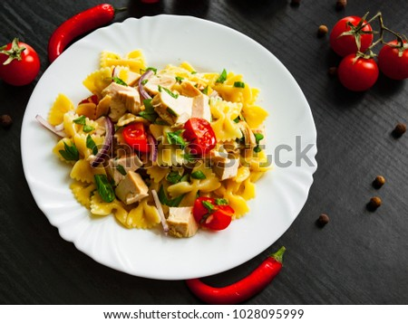 farfalle pasta salad with chicken and vegetables in plate on dark wooden background