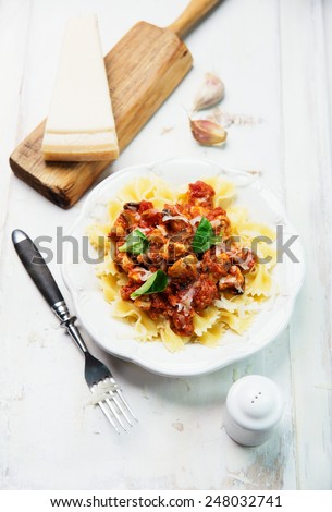 Farfalle pasta with chicken, tomato sauce, mushrooms and parmesan cheese  - stock photo