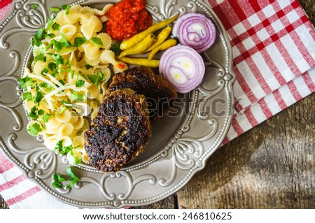 Farfalle topped with tomato sauce, vegetables and meat - stock photo