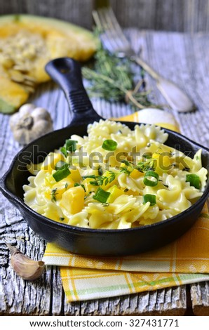 Farfalle with pumpkin,garlic and thyme in cream sauce. - stock photo