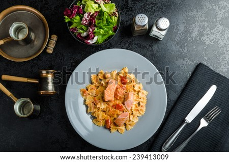 Farfalle with tomato sauce and roasted salmon, fresh endive salad - stock photo