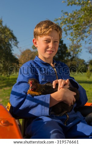 Farm boy with chicken riding on orange tractor