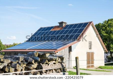 Farm building with innovative roof for alternative energy creation - stock photo