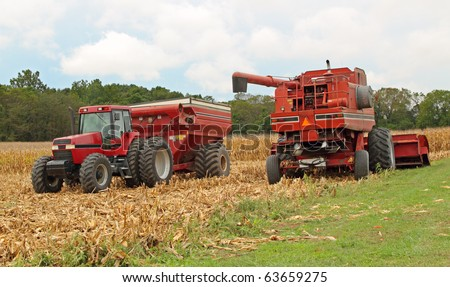 Farm combine and a tractor and wagon harvesting corn