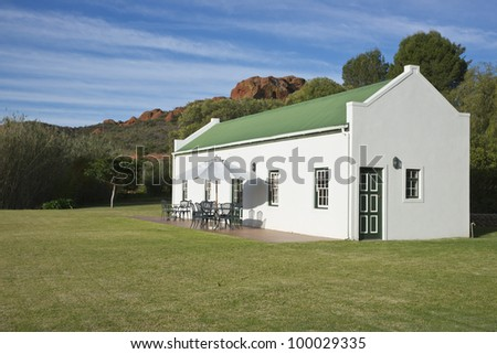 Farm cottage built in traditional Cape architectural style set in landscaped grounds in the Oudtshoorn region of the Western Cape in South Africa. - stock photo