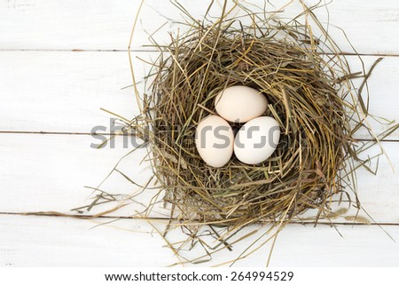 Farm eggs in hay nest on white wooden table background, top view.