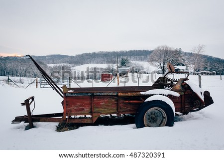 Farm equipment in a snow covered field in rural Carroll County, Maryland.