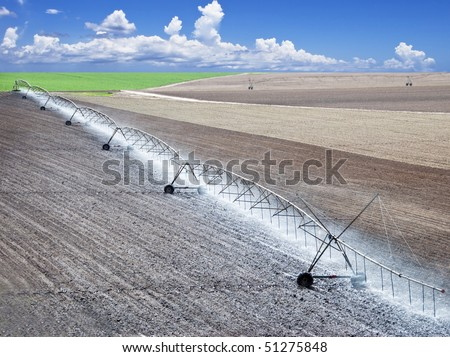 Farm field with modern irrigation system water a newly planted field - stock photo