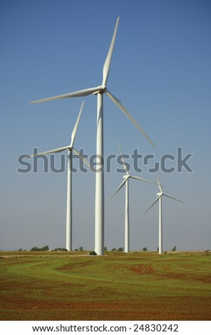 Farm fields are plowed and planted right up to the base of wind turbines.
