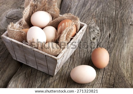 Farm fresh chicken  eggs in box on rustic wooden background - stock photo