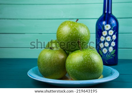 Farm fresh green apples on wood table and bottle with flowers on pastel background - stock photo