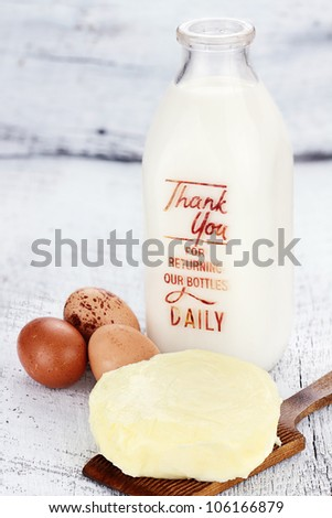 Farm fresh milk, butter, and eggs against a rustic background. Milk is in a vintage glass milk bottle. Shallow depth of field. - stock photo