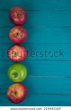 Farm fresh organic red and green apples on wooden table in pastel color with copy space in background - stock photo