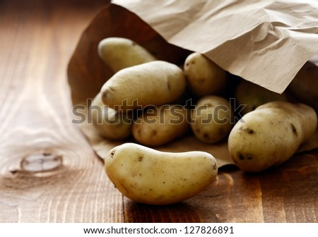 Farm fresh potatoes spilling out of a brown paper packet onto a rustic wooden table on the farmers market - stock photo