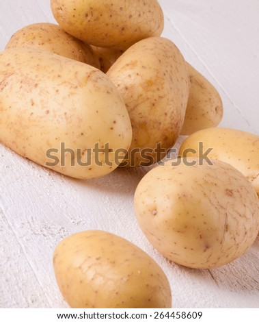 Farm fresh washed whole potatoes for a healthy nutritious cooking ingredient on white painted wooden boards - stock photo