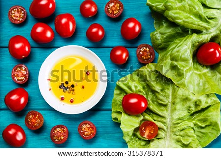 Farm grown tomatos on wooden background with olive oil and salad. Natural food photography with shallow depth of field. - stock photo