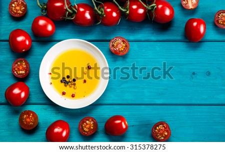 Farm grown tomatos on wooden background with olive oil. Natural food photography with shallow depth of field. - stock photo