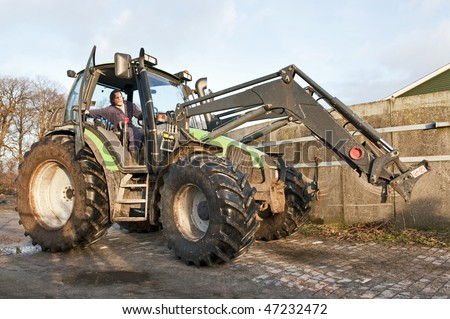 Farm hand behind the wheel of a tractor, closing the door - stock photo