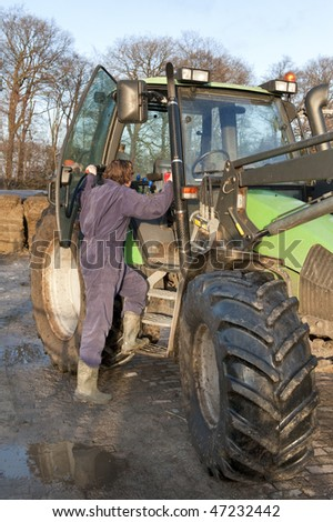 Farm hand boarding a big tractor - stock photo