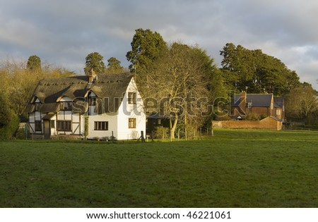 farm house and cottage in a field in the countryside - stock photo