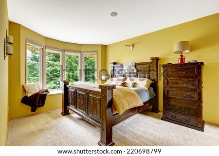 Farm house interior. Luxury bedroom interior. Beautiful wooden high bed with large dresser - stock photo
