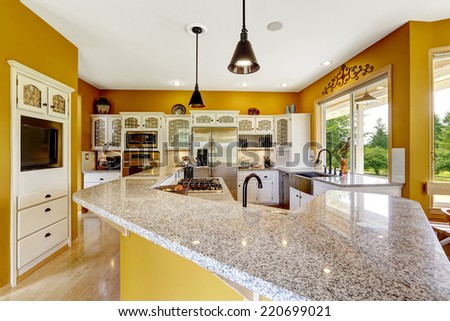 Farm house interior. Luxury kitchen room in bright yellow color with big island and granite top. - stock photo