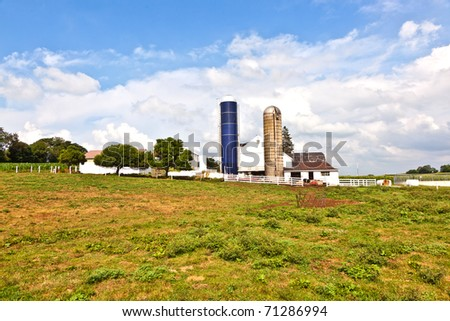 farm house with field and silo in beautiful landscape - stock photo