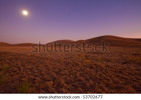 Farm land scene with rolling grassland / pasture hills under a romantic moonlit sky - stock photo