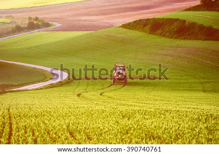 Farm machinery spraying insecticide to the green field, agricultural natural seasonal spring background, vintage retro hipster style - stock photo