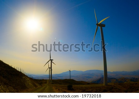 Farm of generators electricity to wind in sunset ray - stock photo
