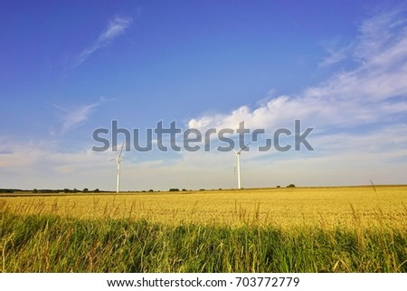 Farm of wind turbines in the field in Poland. Green renewable energy.