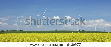 farm of windturbines close to rapeseed field France - stock photo