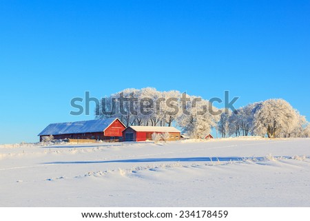 Farm on a hill in a wintry landscape - stock photo