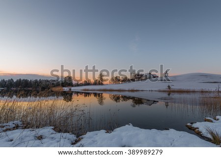 farm on hill at lake in winter while orange sky of sunset