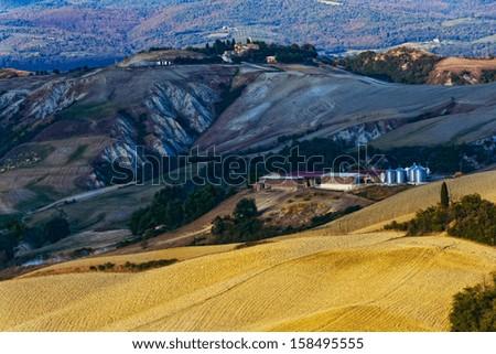 Farm on the clay hills of Crete Senesi in Tuscany, Italy - stock photo