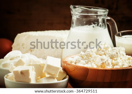 Farm organic dairy products: milk, yogurt, cream, cottage cheese, butter, cottage cheese on a wooden background in rustic style, selective focus - stock photo