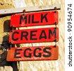 Farm produce sign selling milk, cream and eggs. - stock photo