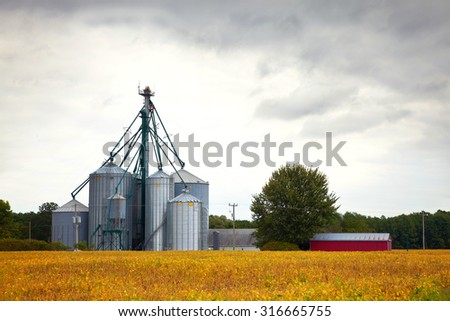 Farm silos storage towers in yellow crops landscape view - stock photo