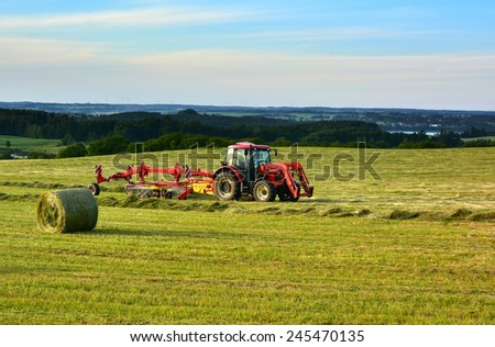Farm tractor on a field - stock photo