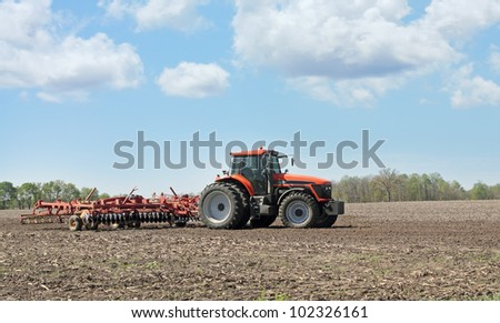 Farm tractor pulling a plow in a farm field - stock photo
