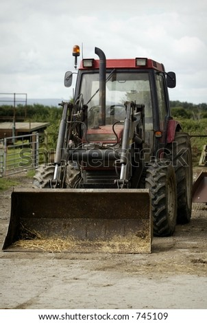 farm tractor with bucket down and hay and straw inside - stock photo