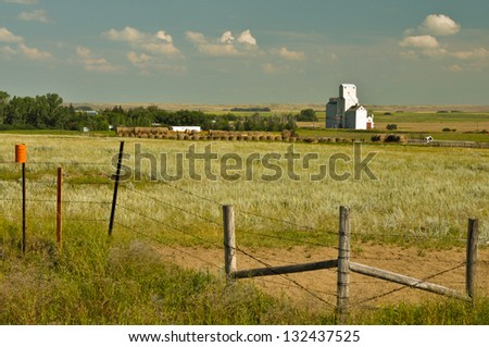 Farm with grain elevators and barbed wire fence - stock photo