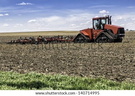 Farm with tractor and plow in the field - stock photo