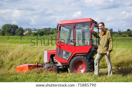 Farm worker with tractor on field  in summer day
