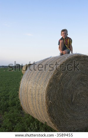 farmboy atop huge haybale, room in sky for text - stock photo