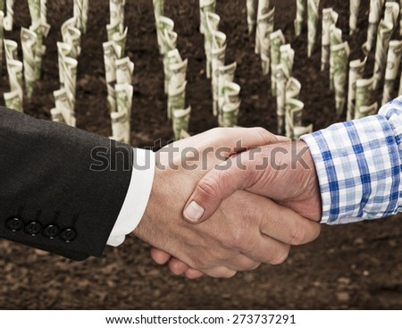 Farmer and businessman shaking hands in front of field of money - stock photo